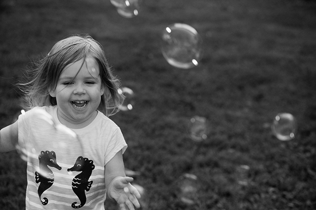 Felicity running with bubbles black and white