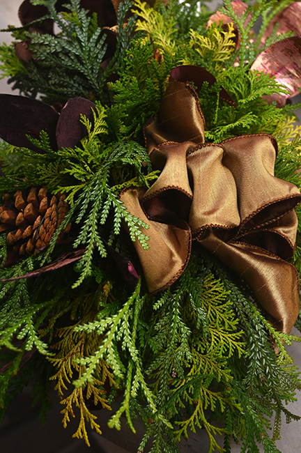 Evergreen Christmas arrangment with brown bow