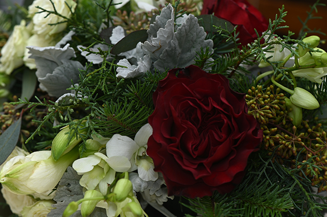 Flower arrangement with garden rose dendrobium orchid and dusty miller